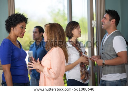 A group of people networking in a lobby.