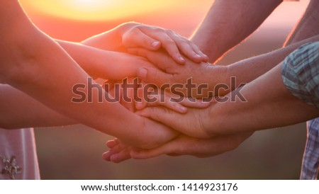 A group of people of different ages puts their hands on one another. Teamwork concept Stock foto ©