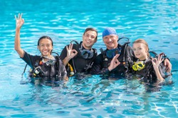 A group of people practice scuba diving in the pool. Diving as an extreme sport