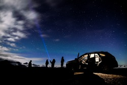 a group of people using flashlight searching for stars on the beautiful night in Iceland  with aurora light shining on the sky