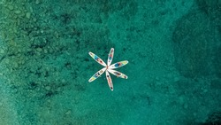 A group of people with SUP stand up paddle boards in the turquoise sea in summer form flowers, view from the drone.