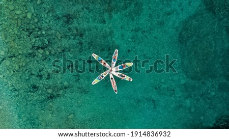 A group of people with SUP stand up paddle boards in the turquoise sea in summer form flowers, view from the drone. Stock photo ©