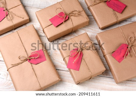 A group of plain brown paper wrapped Christmas presents on a white wood table. The gifts are tied with twine and have blank red gift tags. High angle shot.
