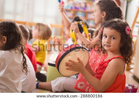 A group of preschool children in a music class.A little girl smiling at camera.