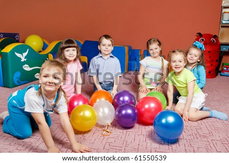 A group of preschool kids in kindergarten with balloons on the floor