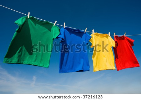 A group of primary colored t-shirts on a clothesline in front of blue sky #37216123
