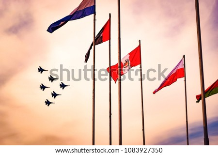 A group of professional pilots of military aircraft shows tricks in the evening sky and waving colorful flags of the World. International Aviation and Space Salon. Zhukovsky, Moscow Region, Russia. #1083927350