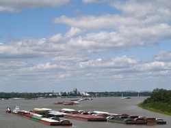 A group of river barges on the Mississippi River transporting cargo downstream.