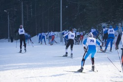 A group of skiers climbs up the snow-covered ski track defocused
