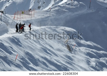 a group of skiers hesitate before attempting a steep descent on a glacier