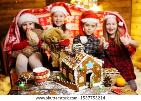 a group of small children friends preschoolers in Santa hats covered with a blanket play with toys and make a gingerbread house on the background of Christmas decor and lights.