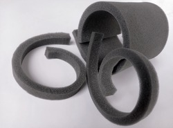 a group of small pieces of black sponge foam with a white background
