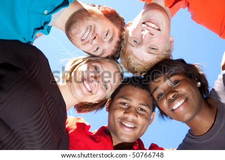 A group of smiling faces of multi-racial college students/friends outside with the blue sky in the background #50766748