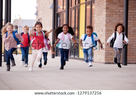 A group of smiling multi-ethnic school kids running in a walkway outside their infant school building after a lesson