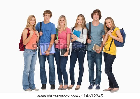 A group of smiling students stand beside each other and wear backpacks and hold notepads while looking at the camera
