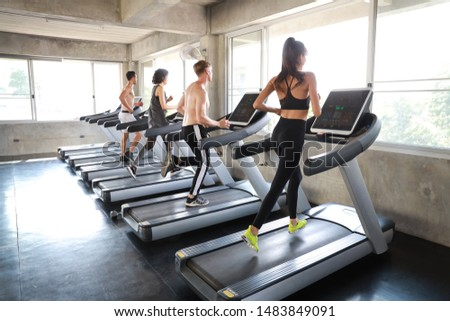 a group of sporty caucasian people exercising with running machine back view image