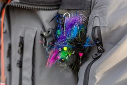 A group of streamers hanging on the jacket of a fly fisherman in Alaska