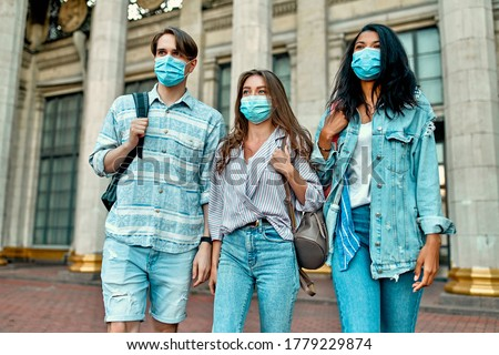 A group of students wearing protective medical masks near the campus. Stock photo ©