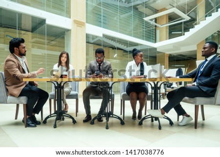 a group of successful afro americans, europeans ,arabic and korean businessman and businesswoman working in the office with large glass windows #1417038776