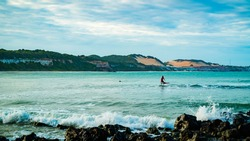 A group of surfers in the water getting ready to surf at the beautiful beach praia do madeiro located near Pipa, Brazil.