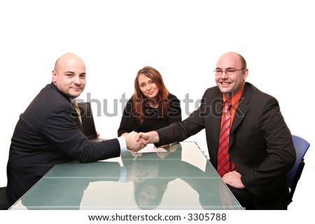 A group of three at a table. Two men shaking hands. Isolated on a white background