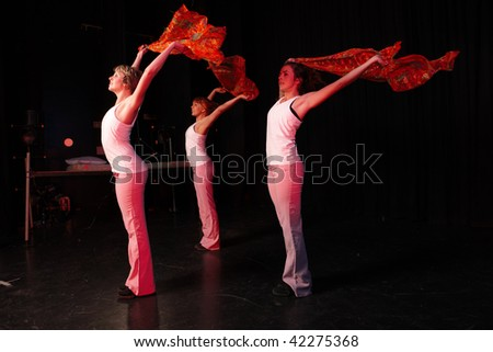A group of three Caucasian female freestyle hip-hop dancers in a dancing training session. Lit with spotlights