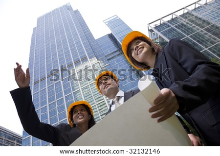 A group of three executives, one man and two women, wearing hard hats review architectural plans in a modern city environment.