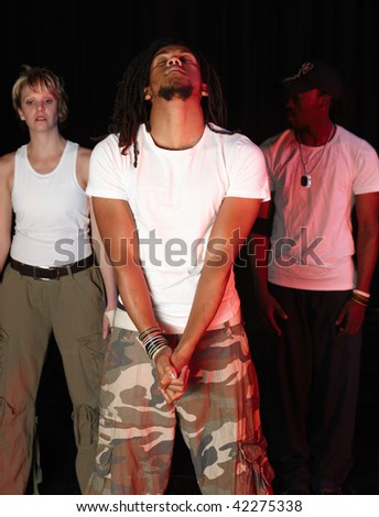 A group of three female and male freestyle hip-hop dancers during dance training session on stage. Lit with spotlights