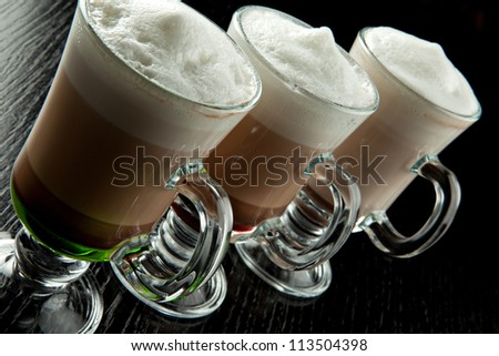A group of three glasses of hot layered alcoholic cocktails, decorated with milk foam on black bar counter - stock photo