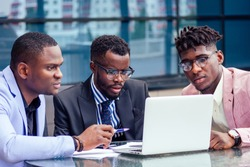 A group of three stylish African American men entrepreneurs in fashion business suits working sitting at table with laptop in a summer cafe outdoors