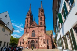A group of tourists are waiting in front of the Basel Minster on a nice sunny day with blue sky. With its red sandstone walls, colourful roof tiles and twin towers it is a very famous landmark.