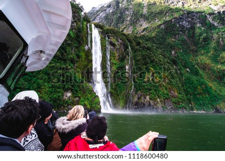 A group of tourists enjoying a stunning scene of nature while cruising into waterfall in Milford Sound, New Zealand. #1118600480