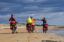 A group of tourists with large backpacks rides mountain bikes along the sandy coast along the mediterranean sea in cyprus