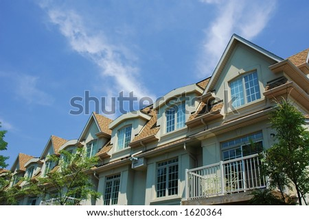 A group of townhouses - homes with green trees, bright blue sky and clouds in background - stock photo