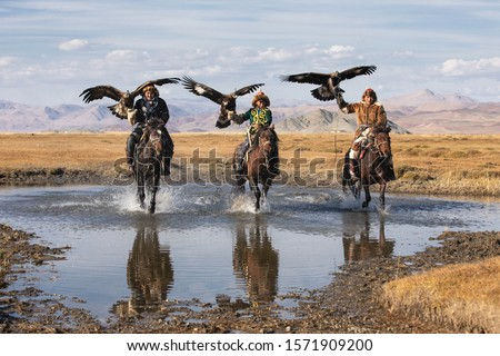 A group of traditional kazakh eagle hunters galloping through the water with their golden eagles. Ulgii, Mongolia.
