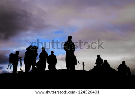 A group of trekkers black silhouette in the cloudy sky background