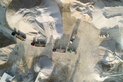 A group of trucks seen from a drone. Some of them are loaded with material and some are empty. Working quarry environment seen from a drone