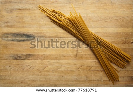 A group of uncooked linguine sits on a cutting board