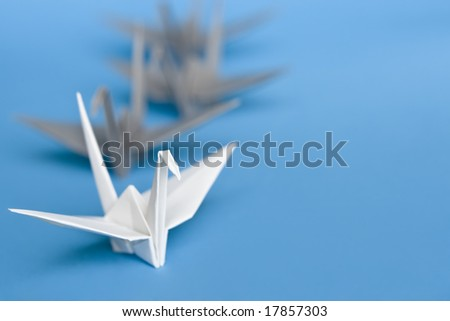 A group of white and grey origami birds forming a queue