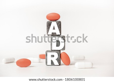 a group of white and red pills and cubes with the word ADR Adverse drug reaction on them, white background. Concept carehealth, treatment, therapy. Stock photo ©