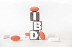 a group of white and red pills and cubes with the word IBD Inflammatory bowel disease on them, white background. Concept carehealth, treatment, therapy.
