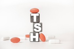 a group of white and red pills and cubes with the word TSH Thyroid stimulating hormone on them, white background. Concept carehealth, treatment, therapy.