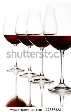 a group of wine glasses filled with red wine, reflections below