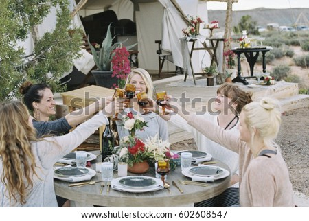 A group of women enjoying an outdoor meal by a large tent, in a desert landscape, raising a toast by clinking glasses