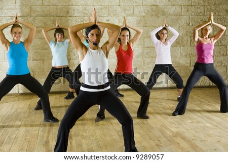 A group of women exercising with fitness instructor in the gym. Focus on the woman in white shirt. Front view.