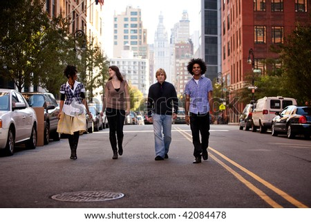 A group of young adults in an uban setting - walking on a road