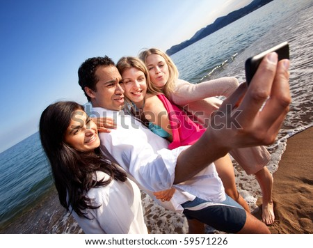 A group of young adults taking a self portrait with a cell phone