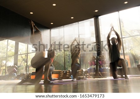 A group of young Asian people who are in good shape Doing yoga on a yoga mat With a trainer doing the example in the gym. They are in a warrior one pose.