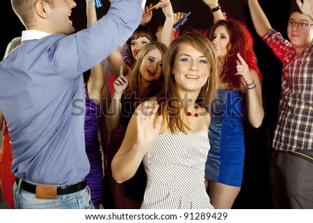 A group of young beautiful people dancing at a disco, smiling