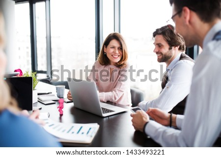 A group of young business people with laptop sitting in an office, talking.